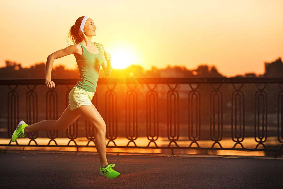Running woman. Runner is jogging in sunny bright light on sunris
